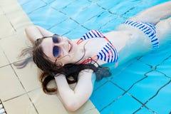 Jong meisje die door de pool rusten Royalty-vrije Stock Foto's