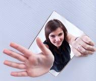 Jong meisje die door een gat in kartonoppervlakte golven stock foto's