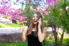 Jong meisje die door smartphone spreken en duimen in de lentepark tonen Royalty-vrije Stock Foto's