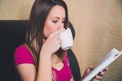 Jong meisje die een boek lezen en koffie drinken Stock Foto