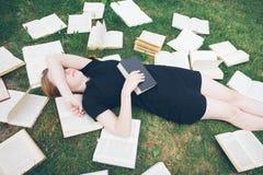 Jong meisje die een boek lezen terwijl het liggen in het gras Een meisje onder de boeken in de de zomertuin royalty-vrije stock foto