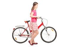 Jong meisje die een fiets duwen Stock Foto's