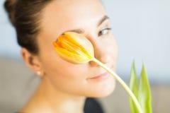 Jong meisje die een gele tulp houden Royalty-vrije Stock Foto's