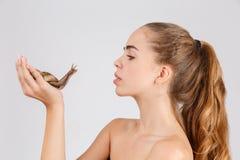 Jong meisje die een grote slak van Ahatina houden en het bekijken Geïsoleerd op wit royalty-vrije stock fotografie