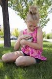 Jong meisje die een huisdierenegel buiten houden stock foto's
