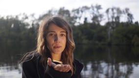 Jong meisje die een luchtkus verzenden naar de camera in een rivier, een boot stock videobeelden