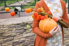 Jong meisje die een oranje pompoen en bloemen houden Stock Foto