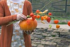 Jong meisje die een oranje pompoen en bloemen houden Royalty-vrije Stock Foto's