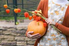 Jong meisje die een oranje pompoen en bloemen houden Stock Foto's