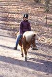Jong meisje die een poney berijden Stock Afbeelding