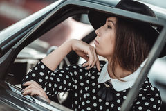 Jong meisje die een retro auto drijven Stock Afbeeldingen