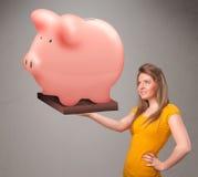 Jong meisje die een reusachtig besparingenspaarvarken houden Stock Afbeeldingen
