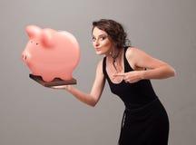 Jong meisje die een reusachtig besparingenspaarvarken houden Royalty-vrije Stock Afbeelding