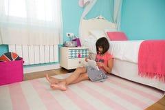 Jong meisje die een tabletpc met behulp van royalty-vrije stock foto's