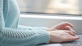 Jong meisje die in een trein reizen en notitieboekje gebruiken Vrouwelijke handen die op toetsenbord van laptop tijdens het berij stock footage