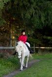 Jong meisje die een wit paard berijden Stock Afbeelding