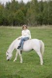 Jong meisje die in een witte sweater en jeans met de benen over elkaar op een wit paard zitten Levensstijlportret Stock Afbeeldingen