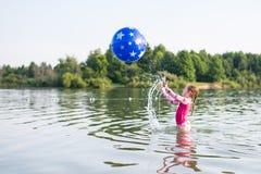 Jong meisje die en bal in meer bespatten werpen stock afbeeldingen