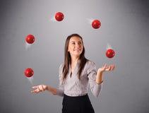 Jong meisje die en zich met rode ballen bevinden jongleren met stock afbeelding