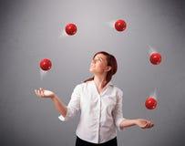 Jong meisje die en zich met rode ballen bevinden jongleren met royalty-vrije stock afbeeldingen