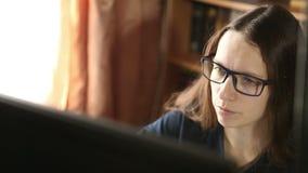 Jong meisje die in glazen bij het computerwerk zitten stock footage