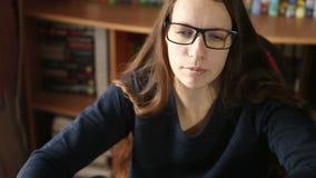Jong meisje die in glazen bij het computerwerk zitten stock video
