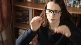 Jong meisje die in glazen bij het computerwerk zitten stock videobeelden