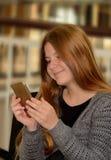 Jong meisje die haar cellphone gebruiken Stock Foto