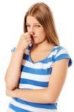 Jong meisje die haar neus houden die iets ruiken het stinken stock afbeelding