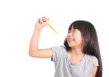 Jong meisje die iets met geel potlood schrijven royalty-vrije stock afbeelding