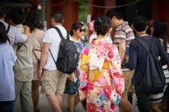 Jong meisje die Japanse kimono dragen die zich voor Sensoji-Tempel in Tokyo, Japan bevinden De kimono is een Japans traditioneel  Stock Foto