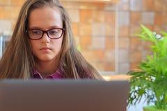 Jong meisje die in keuken met laptop bestuderen stock foto