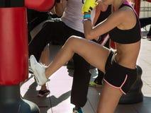 Jong Meisje die Kickboxing met Handschoenen in Geschiktheidsklasse doen met Re Royalty-vrije Stock Fotografie