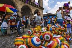 Jong meisje die kleurrijke rubberballen in een straat van de oude stad van Antigua, in Guatemala verkopen Royalty-vrije Stock Foto