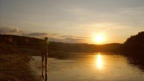Jong meisje die langs strand bespattend water lopen van onder haar voeten, mooie zonsondergang over de rivier, langzame motie Royalty-vrije Stock Afbeeldingen