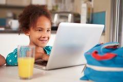 Jong Meisje die Laptop met behulp van om Thuiswerk bij Lijst te doen stock fotografie
