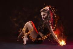 Jong meisje die met brand dansen Stock Afbeelding
