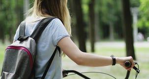 Jong meisje die met de fiets in handen door het park lopen stock video