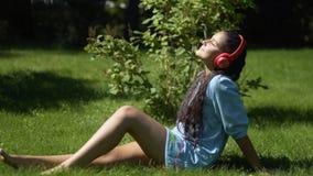 Jong meisje die met lang zwart haar aan muziek op hoofdtelefoons luisteren die smartphonezitting op gras in park in zonnig gebrui stock videobeelden