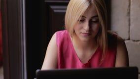 Jong meisje die met laptop werken en bij de koffie zitten stock video