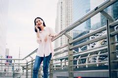 Jong meisje die met smartphone en glimlach roepen die het spreken op openlucht hebben Het concept van de technologie stock fotografie
