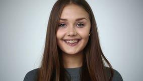 Jong meisje die met steunen op tanden camera en het glimlachen bekijken stock videobeelden