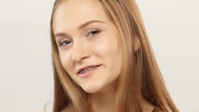 Jong meisje die met steunen op tanden camera en het glimlachen bekijken wit stock footage