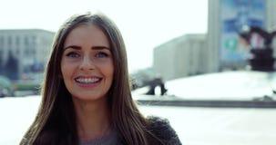 Jong meisje die met steunen op tanden camera en het glimlachen status in de stad bekijken stock videobeelden