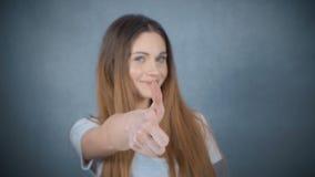 Jong meisje die o.k. gebaar over grijze achtergrond tonen stock video