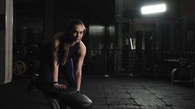 Jong meisje die oefeningen in de gymnastiek doen Geschiktheid Heft ??n handdomoor op Het leunen op de gymnastiekbank stock videobeelden