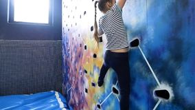 Jong meisje die omhoog bij binnen het beklimmen van muur beklimmen stock footage