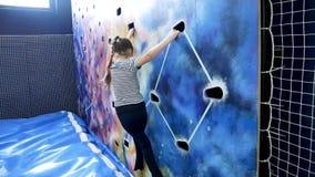 Jong meisje die omhoog bij binnen het beklimmen van muur beklimmen stock video