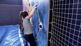 Jong meisje die omhoog bij binnen het beklimmen van muur beklimmen stock videobeelden