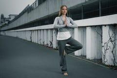 Jong meisje die op één voet mediteren Stock Foto